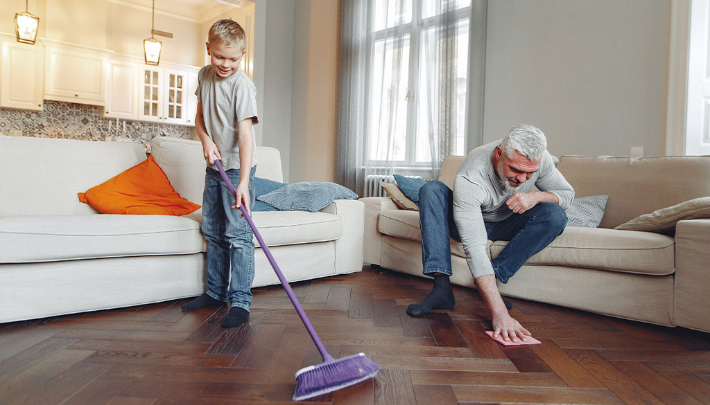 A boy sweeping and man scrubbing the floor for a nice clean home.